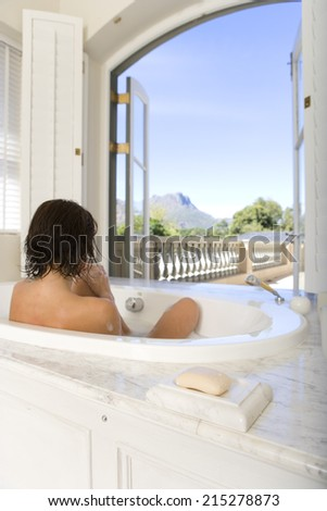 Young woman in bath by window, rear view - stock photo