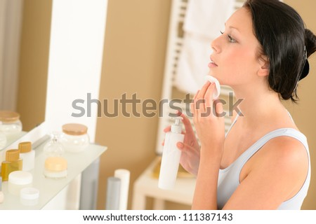 Young woman in bathroom clean face make-up removal looking mirror - stock photo