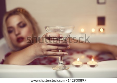 Young woman in bathtub holding cocktail, eyes closed. Focus on hand with wineglass - stock photo
