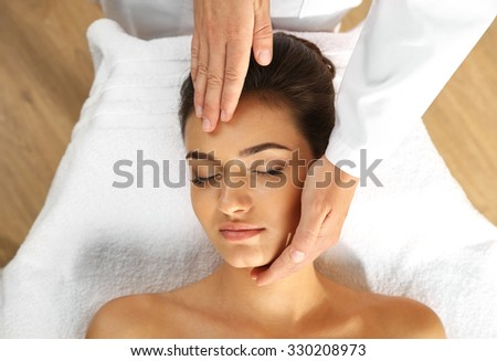 Young woman in beauty spa salon enjoying head massage - stock photo