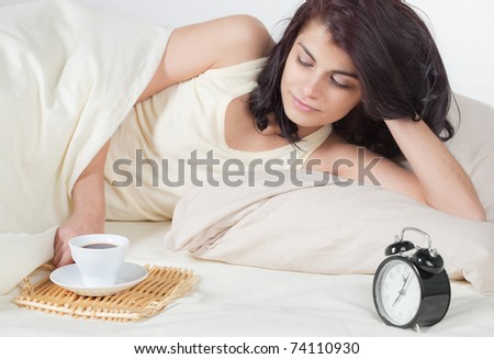 Young woman in bed holding a cup of coffee after she waken up - stock photo