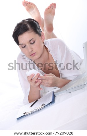 young woman in bed reading a message on her mobile phone - stock photo