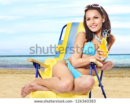 Young woman in bikini drink juice through a straw on beach. - stock photo