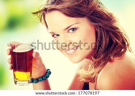 Young woman in bikini drinking ice tea isolated - stock photo