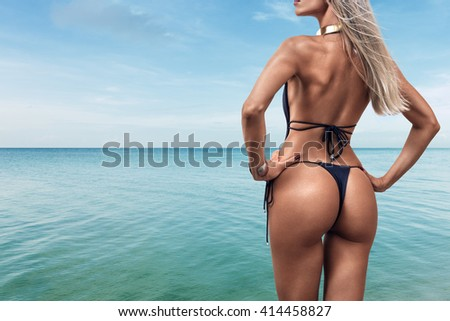 Young woman in bikini looking at sea water on the beach of tropical resort. Rear view - stock photo