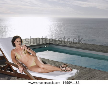 Young woman in bikini lying on deck chair sipping champagne at poolside by ocean - stock photo