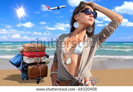 Young woman in bikini on the beach with suitcases and airplane on background - stock photo
