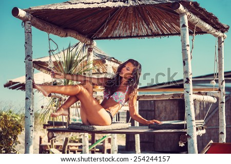 young woman in bikini  sit at shade at seaside beach enjoy in summer hot sunny day, full body shot - stock photo
