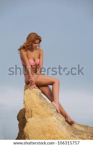 Young woman in bikini sitting on the yellow rock - stock photo