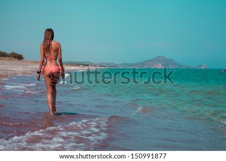 Young woman in bikini walking on a empty beach. horizontal - stock photo