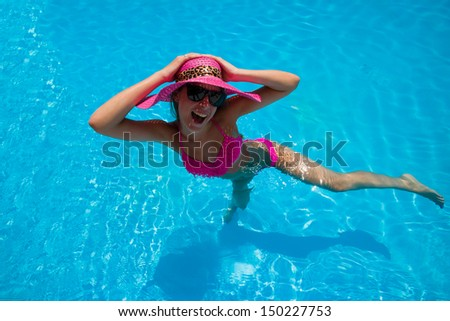 Young woman in bikini wearing a straw hat in the swimming pool making faces - stock photo