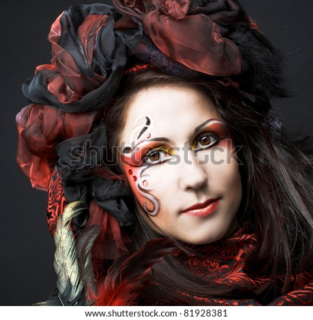 Young woman in black and red silk with mask in her hands - stock photo