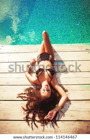 young woman in black bikini lay by the pool - stock photo