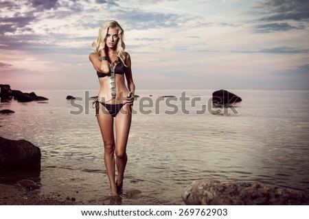 Young woman in black bikini posing in a calm sea while sunset - stock photo