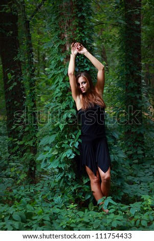 Young woman in black dress at fairy green forest - stock photo
