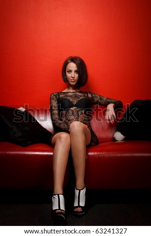 Young woman in black dress sitting on red sofa - stock photo