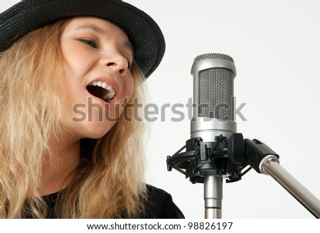Young woman in black hat singing with studio microphone. Isolated on white background. - stock photo
