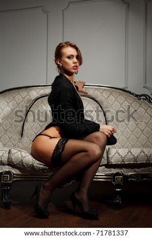 Young woman in black lingerie  sits on the couch - stock photo