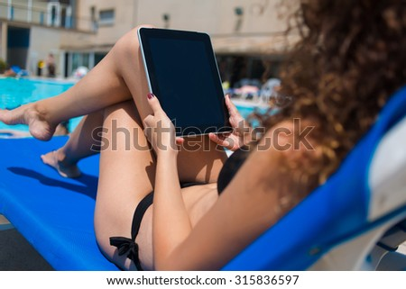 Young woman in black swimsuit holding digital tablet with blank copy space screen for your information content, female in bikini working on her touch pad while lying on sunbed near swimming pool  - stock photo