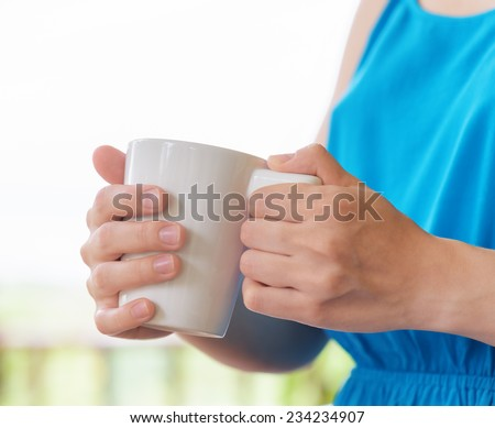 Young woman in blue dress enjoying a mug of beverage. Outdoor portrait. Coffee and tea drinking conception. - stock photo