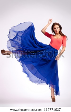young woman in blue dress kicking to her side and looking at the camera - stock photo