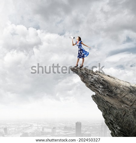 Young woman in blue dress talking in megaphone - stock photo