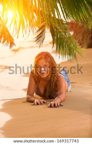 Young woman in blue jeans and bikini top at the beach - stock photo