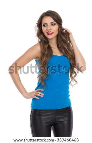 Young woman in blue shirt, black leather trousers posing and looking away. Front view. Three quarter length studio shot isolated on white. - stock photo