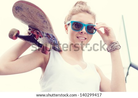 Young woman in blue sunglasses standing with a skateboard in her hands in the daytime. Outdoors - stock photo