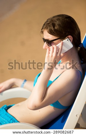 Young woman in blue swimwear and sunglasses sitting on sun deckchair at sunny sandy beach at sea coast, sunbathing in bright sunlight, talking on cellphone - stock photo