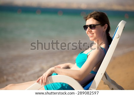 Young woman in blue swimwear and sunglasses sitting on sun deckchair at the sandy beach at sea coast, sunbathing in bright sunlight, looking at sea with joyful smile - stock photo