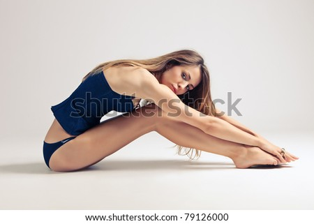 young woman in blue underwear sit on the floor, side view, studio shot, little amount of grain added - stock photo