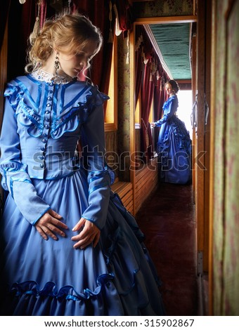 Young woman in blue vintage dress late 19th century standing near window in corridor of retro railway vehicle - stock photo