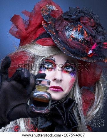 Young woman in bright creative image and with little bottle - stock photo
