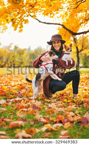 Young woman in brown hat with two little dogs playing outside in autumn leaves - stock photo