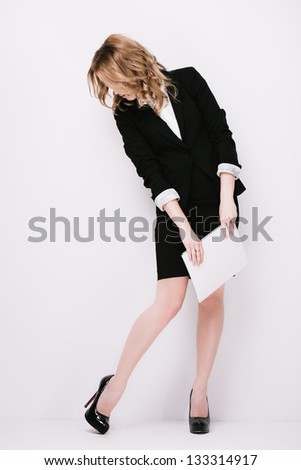 Young woman in  business suit with blank paper, looking on her foot - stock photo