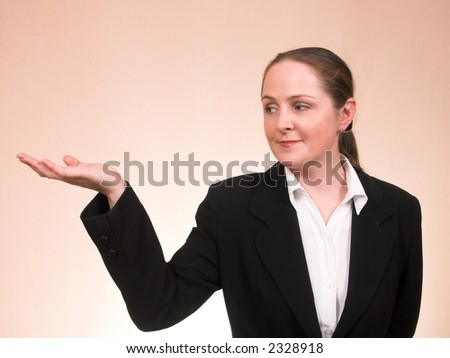 Young woman in business suite showing something on a palm smiling with copyspace - stock photo