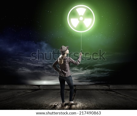 Young woman in casual holding balloon with radioactivity sign - stock photo