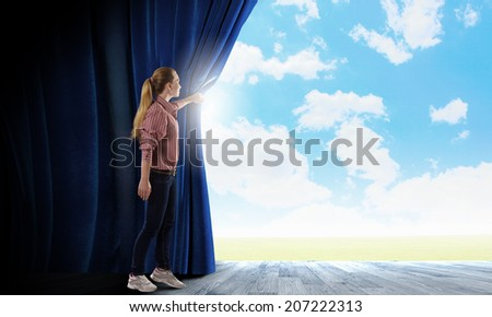 Young woman in casual opening blue curtain and looking at clear sky - stock photo