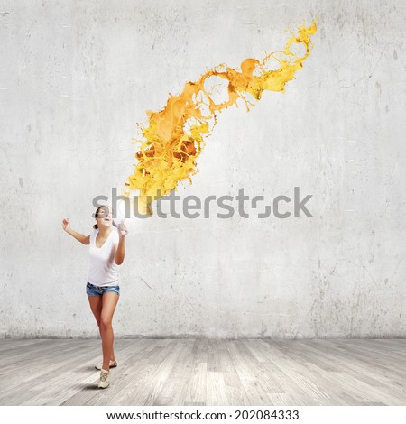 Young woman in casual speaking in megaphone with colorful splashes flying out - stock photo