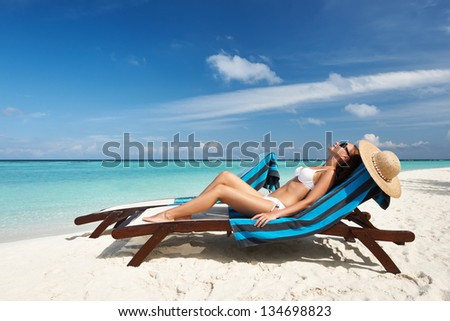 Young woman in chaise lounge at the beach - stock photo