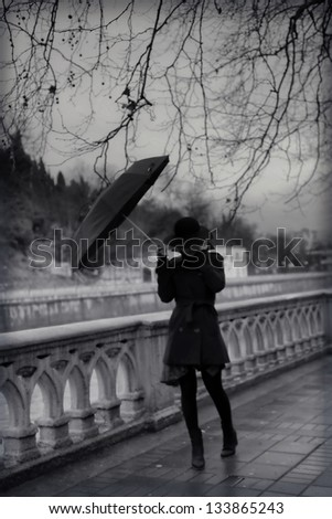 Young woman in coat with umbrella - stock photo