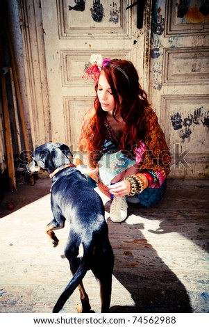 young woman in colorful clothes play with dog, indoor shot, - stock photo