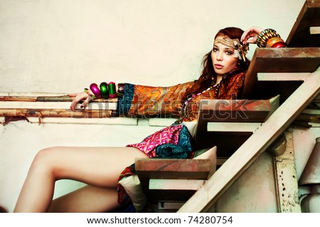 young woman in colorfull summer clothes sit on stairs indoor shot - stock photo