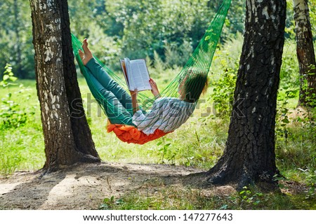 Young woman in dark sunglasses lies in hammock suspended between two thick birches and reads book - stock photo