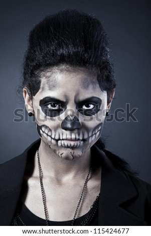 Young woman in day of the dead mask skull face art. Halloween face art with fog on black background - stock photo