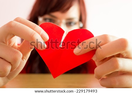 Young woman in depression tearing heart - stock photo