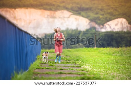 Young woman in dress and blue wellies walk her beagle dog in green nature - stock photo