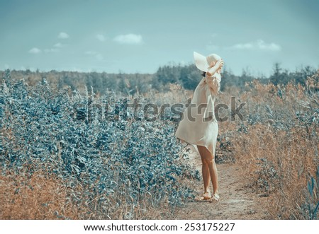 Young woman in dress and hat with wide brim walking in summer fairy park - stock photo