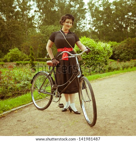 Young woman in dress posing with retro bicycle in the park. Vintage style. - stock photo